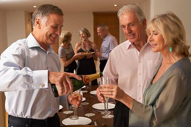 Hombre que se sirven con champán A sus huéspedes A la cena - foto de stock