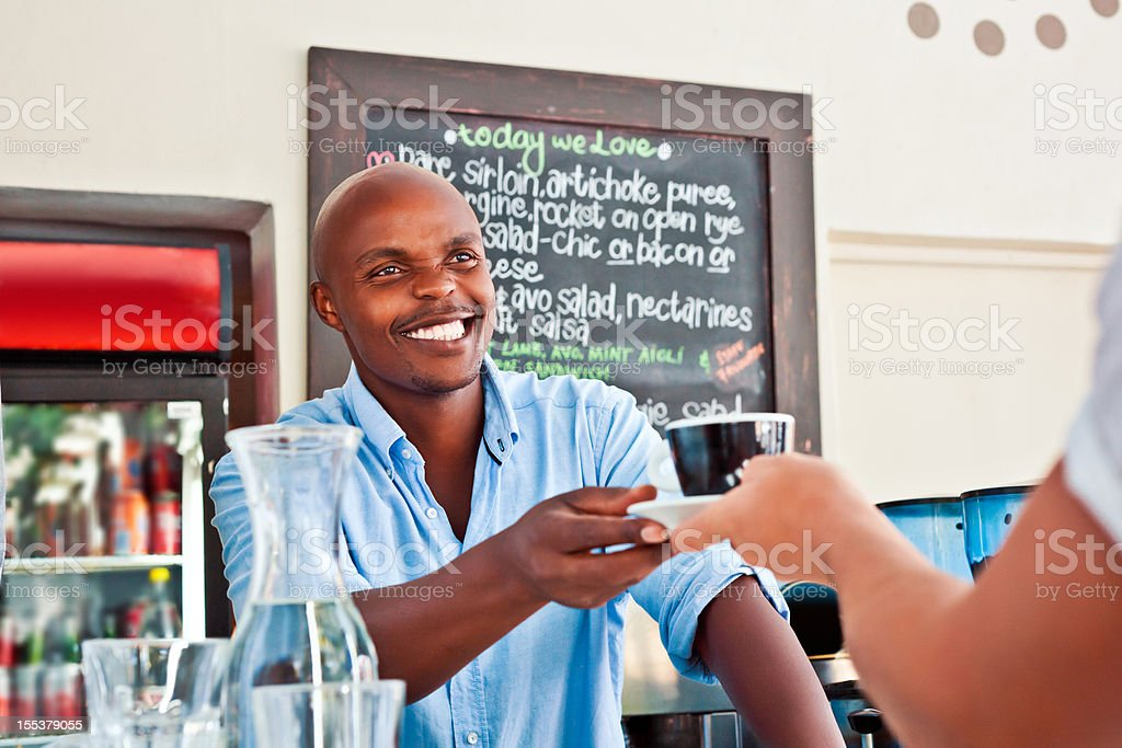Man serving coffee Friendly african man serving coffee in coffee shop. Adult Stock Photo