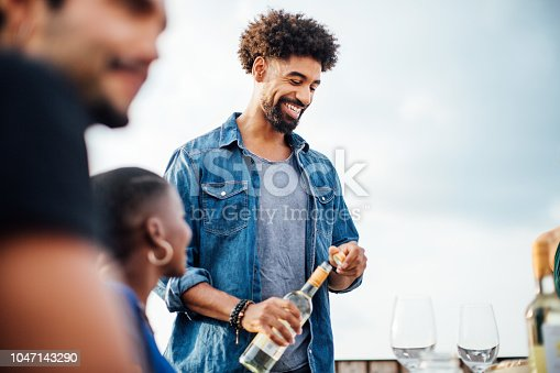 Happy young man serving drinks to friends at rooftop party. Group of young people having a party on rooftop.
