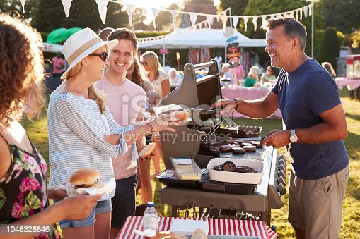 istock Man Serving On Barbeque Stall At Summer Garden Fete 1048326646