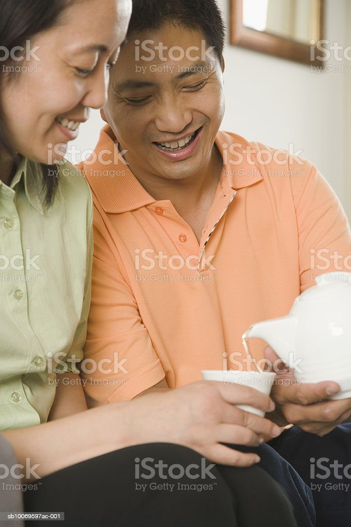 Man serving tea to woman, smiling photo libre de droits