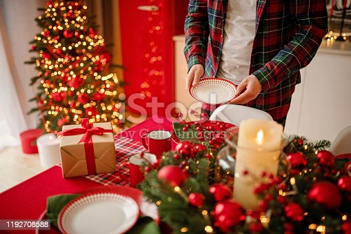 1059144984 istock photo man sets a beautiful decorated winter table for a festive dinner. Merry Christmas and Happy New Year. 1192708588