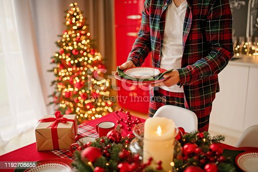1059144984 istock photo man sets a beautiful decorated winter table for a festive dinner. Merry Christmas and Happy New Year. 1192708655