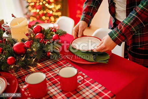 1059144984 istock photo man sets a beautiful decorated winter table for a festive dinner. Merry Christmas and Happy New Year. 1192708732