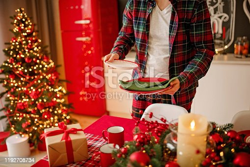 1059144984 istock photo man sets a beautiful decorated winter table for a festive dinner. Merry Christmas and Happy New Year. 1192708734