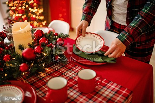 1059144984 istock photo man sets a beautiful decorated winter table for a festive dinner. Merry Christmas and Happy New Year. 1192708785