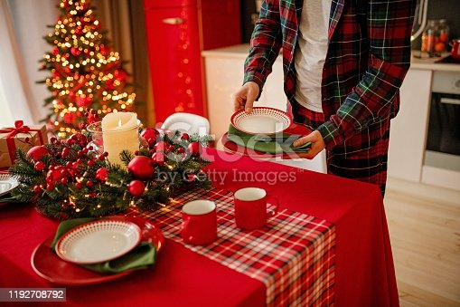 1059144984 istock photo man sets a beautiful decorated winter table for a festive dinner. Merry Christmas and Happy New Year. 1192708792