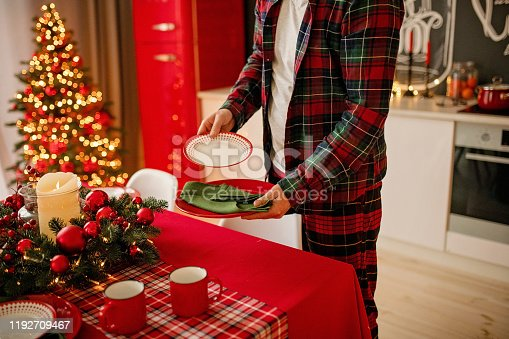 1059144984 istock photo man sets a beautiful decorated winter table for a festive dinner. Merry Christmas and Happy New Year. 1192709467
