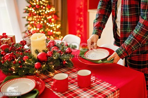 1059144984 istock photo man sets a beautiful decorated winter table for a festive dinner. Merry Christmas and Happy New Year. 1192709587