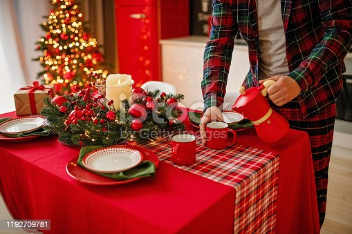 1059144984 istock photo man sets a beautiful decorated winter table for a festive dinner. Merry Christmas and Happy New Year. 1192709781