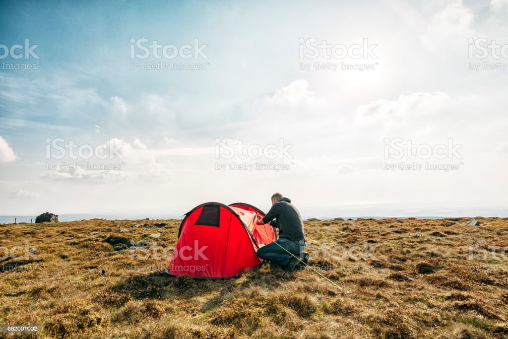 Man setting up a Tent in a remote location. stock photo