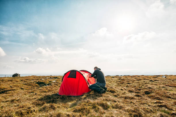 man setting up a tent in a remote location. - tent stock photos and pictures