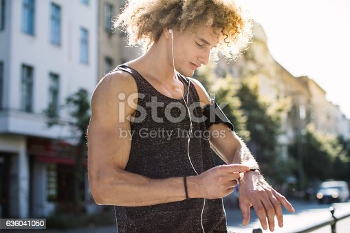 Young man setting up smartwatch for running session in morning