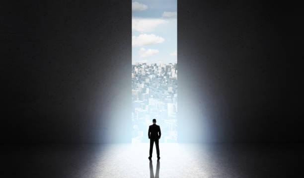 大きなドアの前で新しい都市の建物を開始する男の影 - 機会 ストックフォトと画像