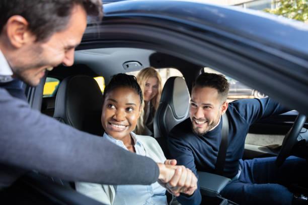 hombre sacudiendo hanks con amigos sentados en el coche - uso compartido del coche fotografías e imágenes de stock