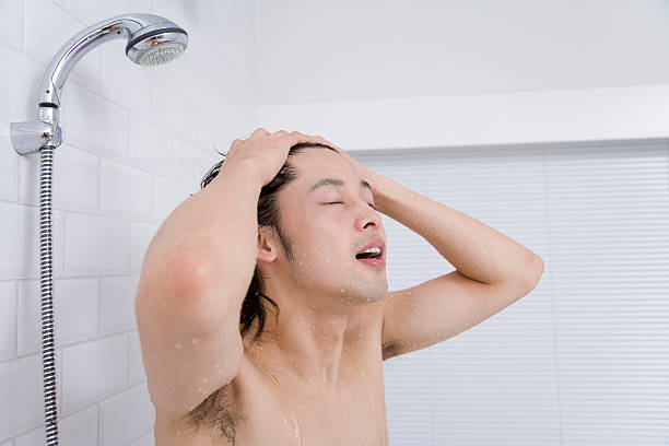 Man shampooing his head in shower stock photo
