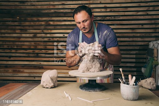 Craftsman shaping sculpure in his studio. Man doing sculpture with clay.