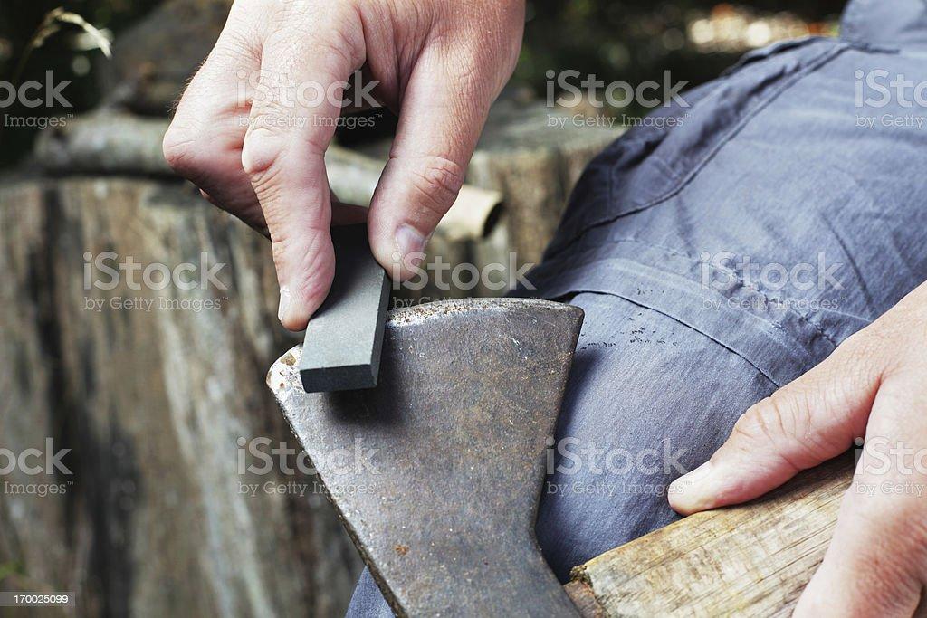 Man Sharpening Axe with Whetstone stock photo