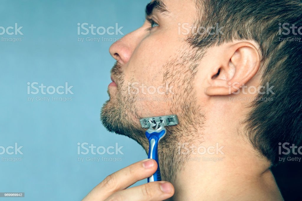 A man shaves a shaving machine without using foam, soap and cream. Shave dry. Advertising poster, with space for text. copy space. stock photo