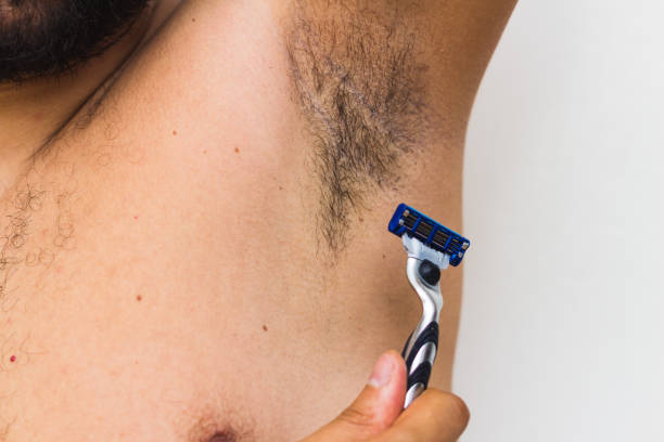 man shaving armpits . holding razor in hands stock photo
