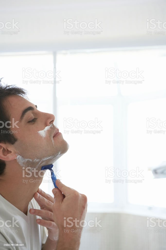 Man shaving face, head back, side view stock photo