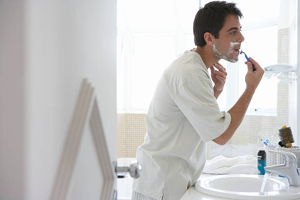 Man shaving face in bathroom mirror, side view stock photo