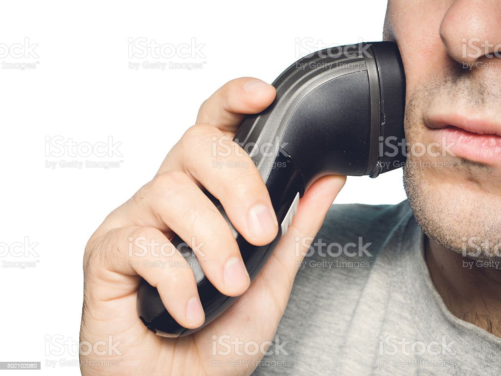 man shaving his beard off with an electric shaver stock photo