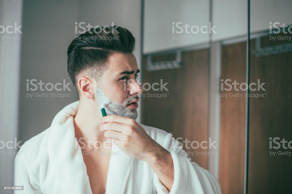 Man shaving his beard stock photo