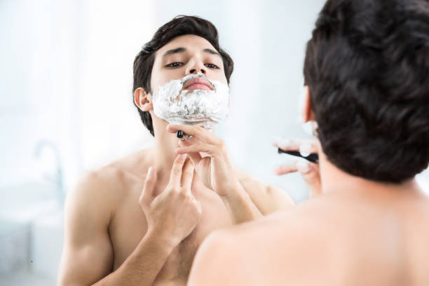 Man shaving in the bathroom. Man shaving in the bathroom. shaved head stock pictures, royalty-free photos & images