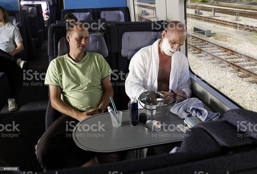 Man shaving on train royalty-free stock photo