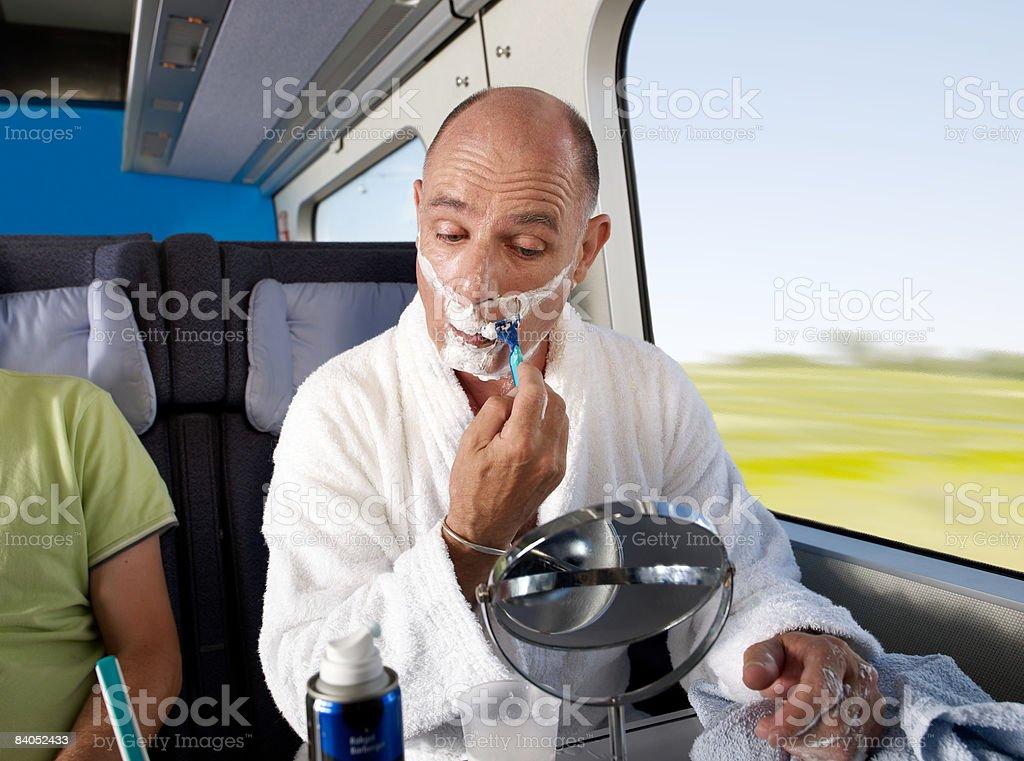 Man shaving on train royaltyfri bildbanksbilder