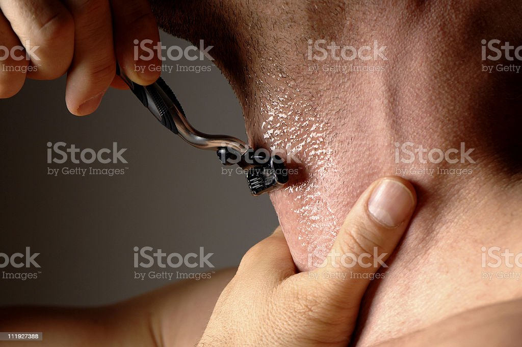 Man Shaving with Razor Holding Throat Dark Gray Background royalty-free stock photo