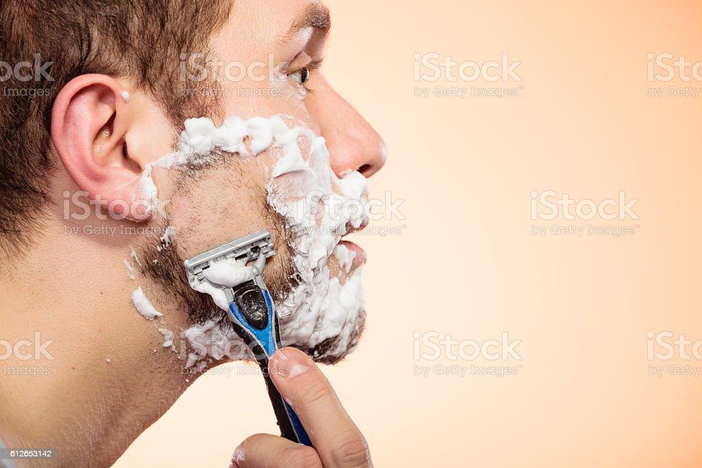 Man shaving with razor stock photo