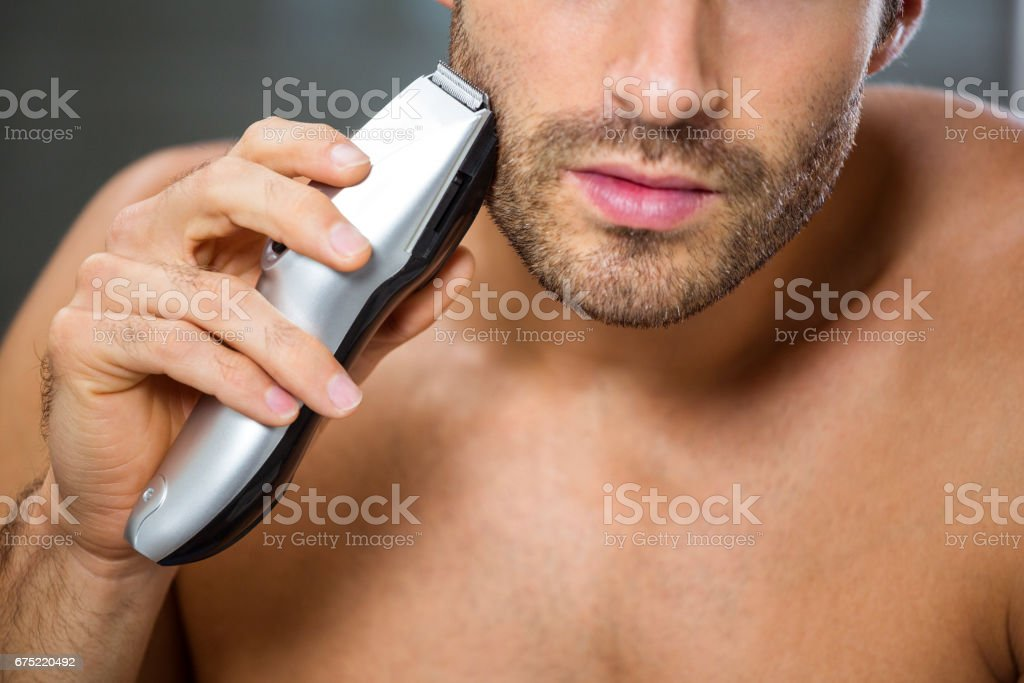 Man shaving with trimmer royalty-free stock photo