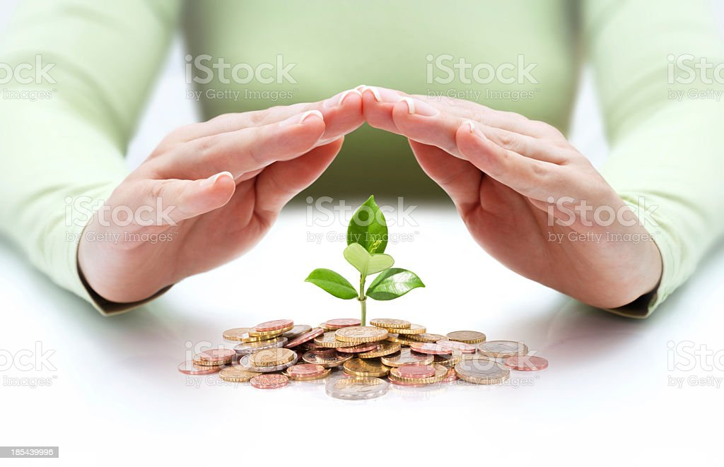 A man shields a plant sprouting from money stock photo