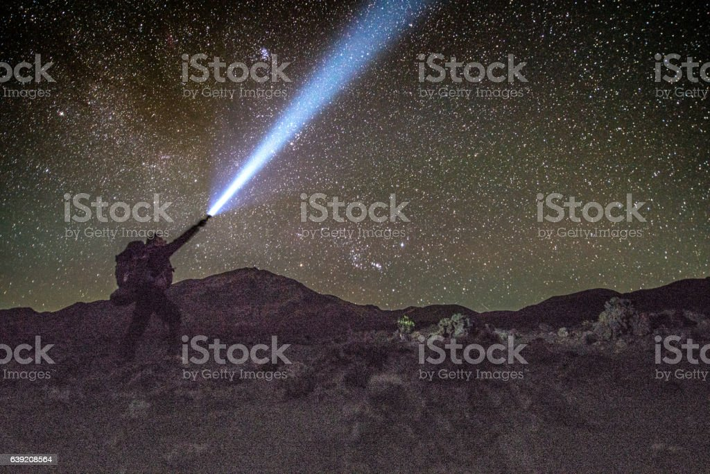 Man shining a torch into a star lit night sky. stock photo