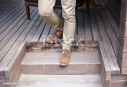 man in the shoes goes down the wooden steps of the house
