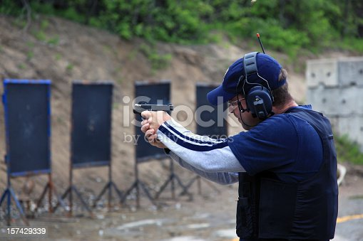 A young adult male shooting a 9mm handgun at an outdoor shooting range. He is wearing a navy blue shirt and hat, and he is wearing appropriate headphones to protect his ears from the repetitive loud noise. The man is taking aim and is getting ready to shoot the target.