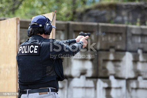Male police officer training at an outdoor firing range wearing his police vest, blue baseball cap, jeans with black belt, long-sleeved blue shirt, and ear protection and firing a 9mm handgun.