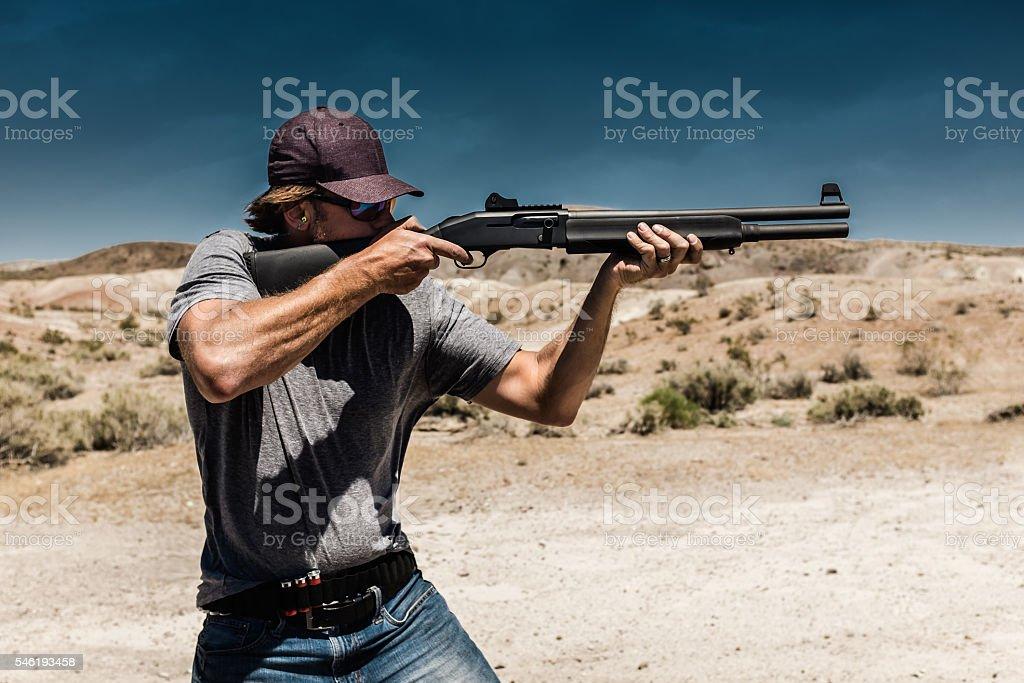 Man Shooting A 12 Gauge Shotgun stock photo