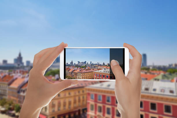A man shooting a photo of aerial view of Poland capital A man is making a photo of view from above of the Poland capital - Warsaw in summer day on a mobile phone taken on mobile device stock pictures, royalty-free photos & images