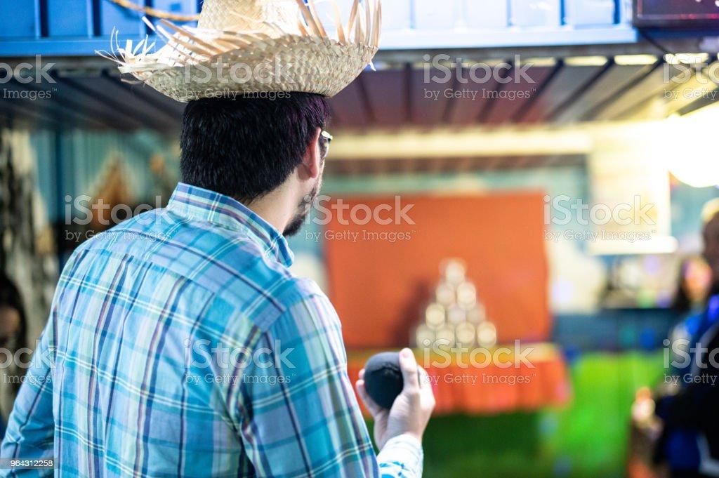 Homem a atirar latas com jogo de bolas na tradicional Festa Junina brasileira - foto de acervo
