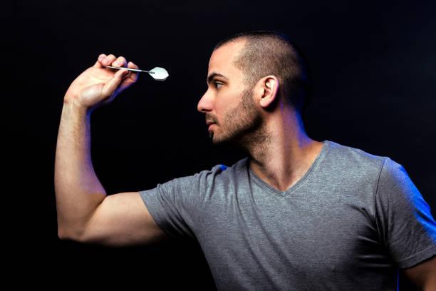 Man shooting darts stock photo