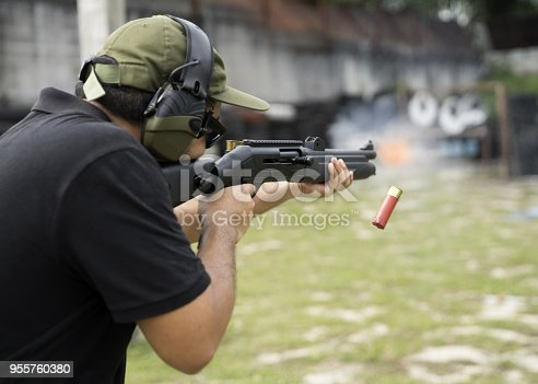 istock Man shooting on an outdoor shooting range, selective focus 955760380