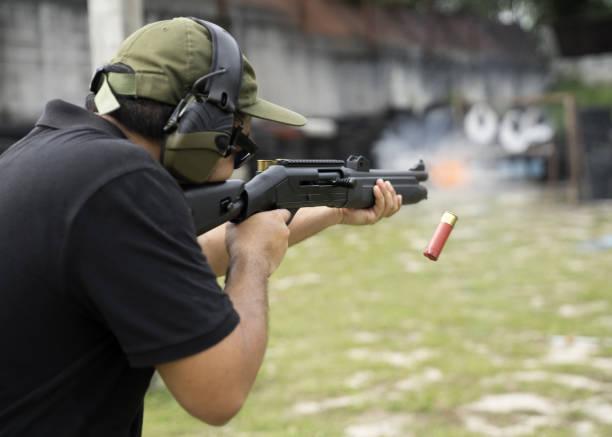 man schieten op een buiten schietbaan, selectieve aandacht - gun shooting stockfoto's en -beelden