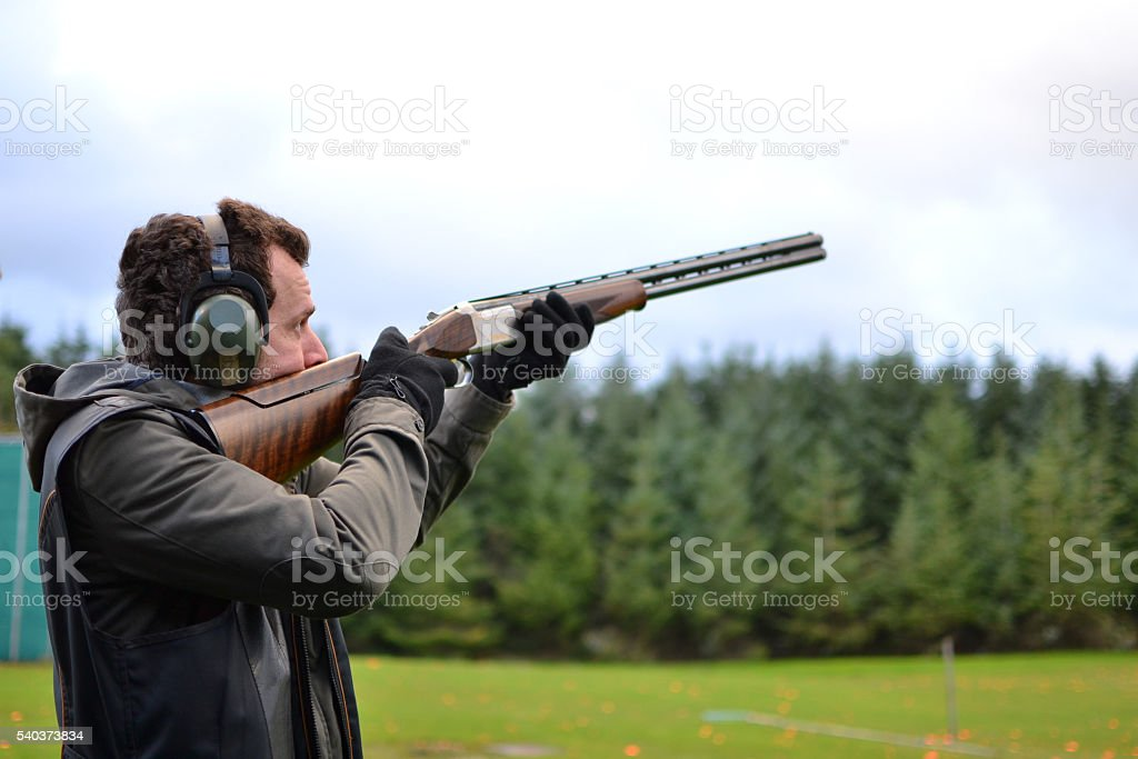 man shooting shotguns at clay pigeon outdoors stock photo