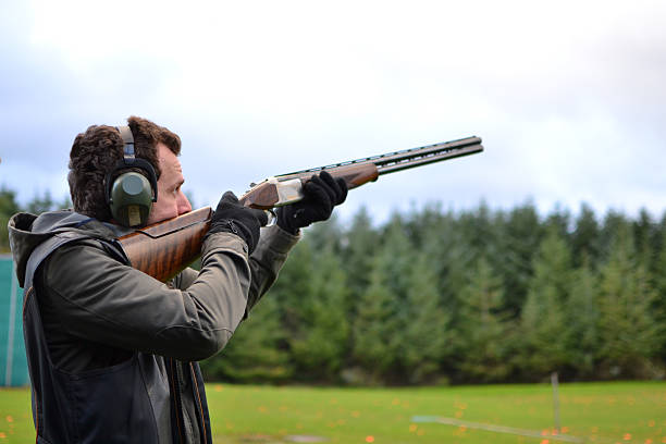 man shooting shotguns at clay pigeon outdoors Shot in the Isle Of Man shooting a weapon stock pictures, royalty-free photos & images