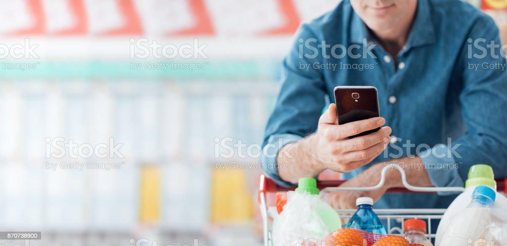 Man einkaufen und mobile apps verwenden – Foto