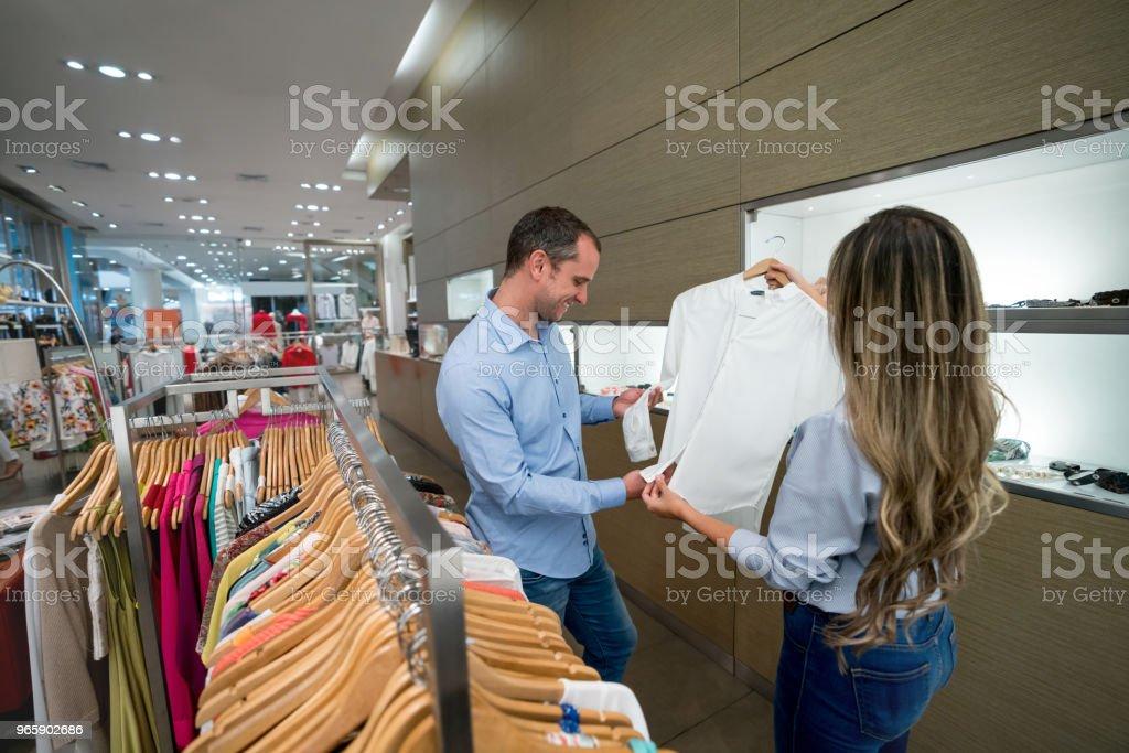 Man winkelen bij een praten met de verkoopster kledingwinkel - Royalty-free 30-39 jaar Stockfoto