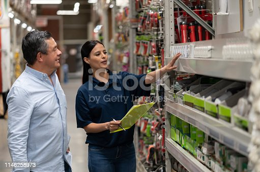 Happy Latin American man shopping at a home improvement store and talking to a saleswoman – business concepts